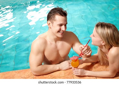 Photo of happy couple in swimming pool chatting with one another