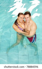 Photo of happy couple in swimming pool embracing and looking at camera