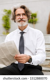 Photo of happy elderly businessman in eyeglasses holding newspaper while sitting outdoors