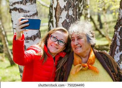 Photo of happy elderly woman with her daughter taking selfie