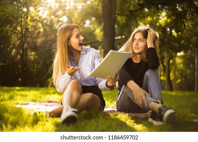 Photo of happy excited girl try to force her displeased confused friend sister to education students sitting in the park outdoors on grass holding copybook doing homework.