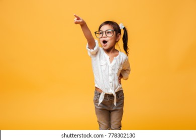 Photo of happy excited little girl child wearing glasses standing isolated over yellow background. Looking aside pointing.