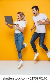 Photo of happy excited young loving couple jumping isolated over yellow wall background using laptop computer.