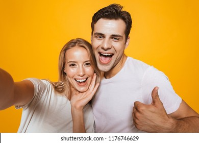 Photo of happy excited young loving couple standing isolated over yellow wall background take a selfie by camera showing thumbs up gesture.