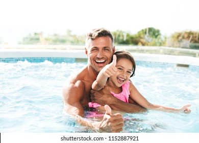 Photo of happy family father with daughter smiling while swimming in pool outdoor during summer vacation