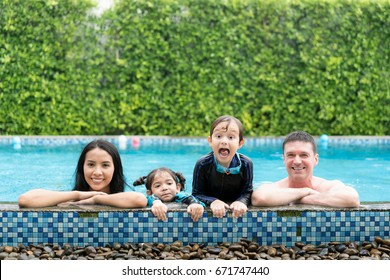 Photo of happy family in swimming pool smiling at camera in summer holiday resort. Happy family summer vacation with father, mother, daughter and brother.