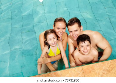 Photo of happy family in swimming pool smiling at camera