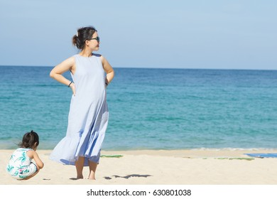 photo of Happy family.Pregnant mother and daughter relaxing and playing on the beach,Happy pregnant woman, little child daughter and tummy mother in summer day.