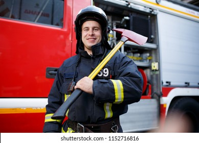 Photo of happy fireman with hammer against fire machine