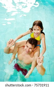 Photo of happy girl sitting on her father shoulders in pool