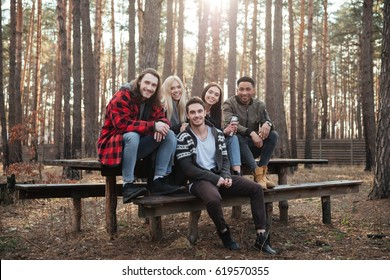 Photo of happy group of friends sitting outdoors in the forest. Looking at camera and posing.