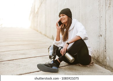 Photo of happy handicapped woman in casual wear having bionic leg sitting on concrete floor outside and talking on mobile phone