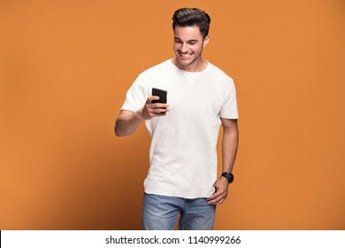 Photo of happy handsome man holding mobile phone in hand, texting. Young guy with big toothy smile posing on yellow background wearing white t-shirt.