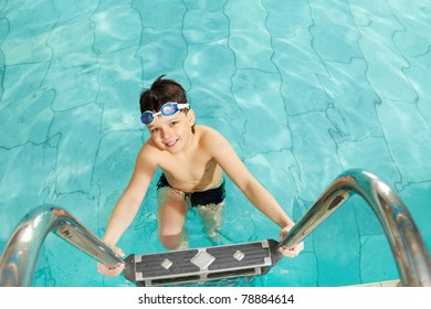 Photo of happy lad in pool smiling at camera