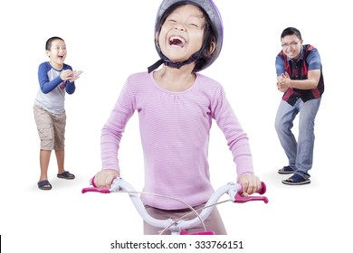 Photo of happy little girl wearing helmet and try to ride a bicycle with her family on the back, isolated on white background