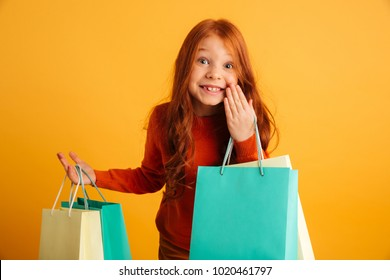 Photo of happy little redhead girl with freckles standing isolated over yellow background holding shopping bags. Looking camera.