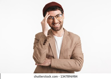 Photo of happy man 30s wearing hipster hat smiling and touching his forehead isolated over white background