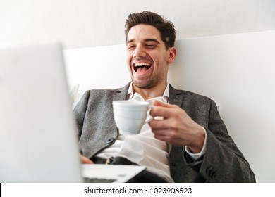 Photo of happy man in businesslike clothes bursting into laughter while resting in bed with laptop and drinking coffee