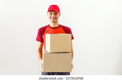 Photo of happy man from delivery service in red t-shirt and cap giving food order and holding two boxes isolated over white background
