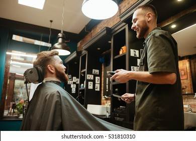 Photo of happy man getting haircut by hairdresser with electric razor while sitting in barbershop. Look aside.