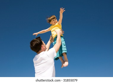 Photo of happy man raising his cute son against bright blue sky