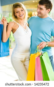 Photo of happy man and woman standing together and carring shopping bags in the shop