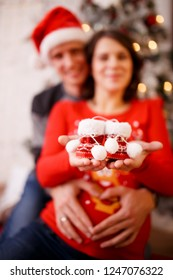 Photo of happy married couple with booties on background of Christmas decorations