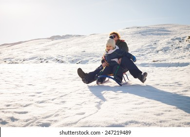 photo of happy mother and child playing in the snow with a sledge in a sunny winter day