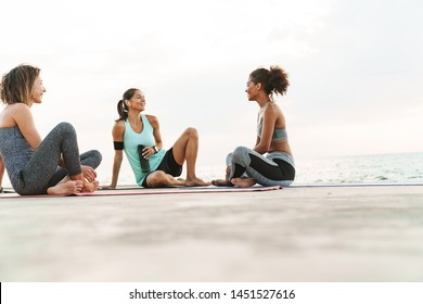 Photo of happy multiethnic sportswomen in tracksuits smiling and talking while sitting on yoga mats by seaside in morning