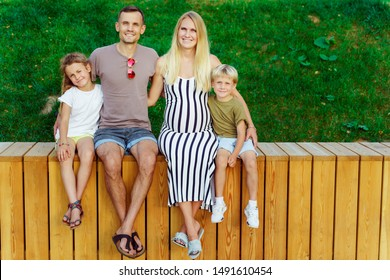 Photo of happy parents and two children sitting on wooden fence