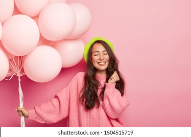 Photo of happy pleased brunette Asian lady stands with balloons, enjoys cool party with friends, wears beret and loose jumper, celebrates anniversary, poses against pink background. Festive event