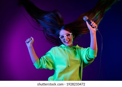 Photo of happy positive cheerful young woman raise mic fist good mood fly hair isolated on neon purple color background