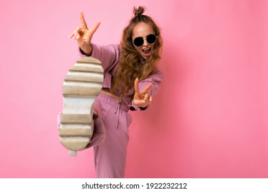 Photo of happy positive young attractive blonde curly woman with sincere emotions wearing trendy pink sportswear and sunglasses isolated on pink background with copy space and having fun
