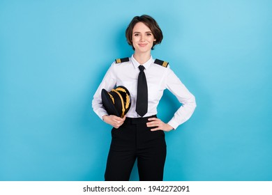 Photo of happy pretty young woman hold hand waist good mood pilot isolated on pastel blue color background