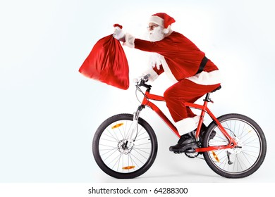 Photo of happy Santa Claus on bike with red sack in stretched arm