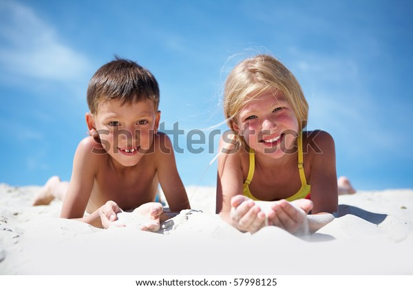 Photo of happy siblings lying on beach and playing with sand on summer vacation