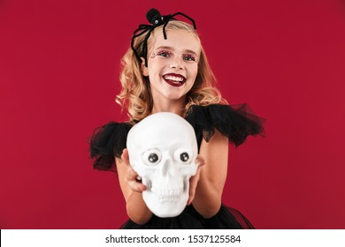 Photo of happy smiling little girl in carnival halloween costume isolated over red wall background holding skull.