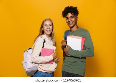 Photo of happy students guy and girl 16-18 wearing backpacks smiling and holding exercise books isolated over yellow background