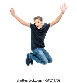 Photo of happy teenage boy jumping with hands up looking at camera.