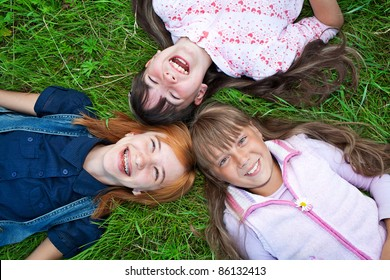 Photo of happy three girls lying on green grass laughing at camera