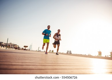 Photo of a happy two athlete running at sunrise beach.