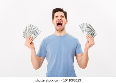 Photo of happy winner man in casual t-shirt holding two fans of money dollar banknotes isolated over white wall