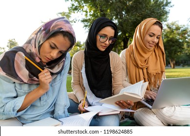 Photo of a happy young arabian women students using laptop computer and holding books in park.