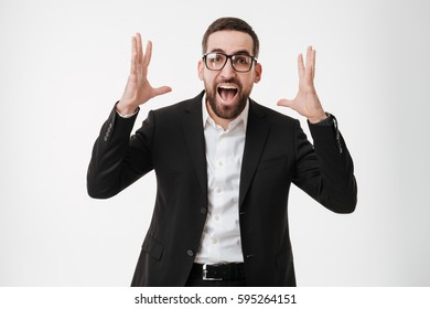 Photo of happy young bearded businessman wearing eyeglasses over white background while gesturing with hands. Looking at camera.
