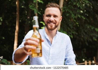 Photo of happy young bearded man outdoors drinking beer looking camera.