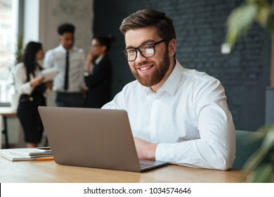 Photo of happy young caucasian businessman sitting indoors using laptop computer. Looking camera.