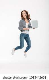 Photo of happy young lady jumping isolated over white wall background using laptop computer. Looking camera.