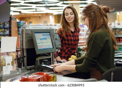 Photo of happy young lady standing in supermarket shop near cashier's desk. Looking aside.