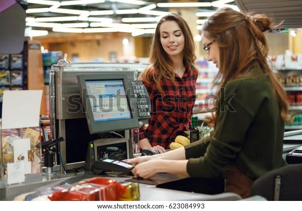 Foto von einer glücklichen jungen Dame, die im Supermarkt in der Nähe des Kassenschreibens steht. Blick zur Seite.