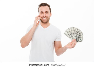 Photo of happy young man standing isolated over white background talking by mobile phone. Looking camera holding money.